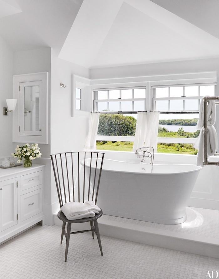 Badezimmer in Weiß gestalten, Badewanne aus Keramik und Holzmöbel, großes Fenster