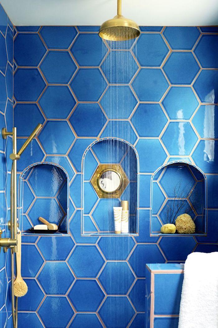 Bad Gestaltung in Blau, sechseckige Fliesen, Nischen für Badutensilien, goldene Dusche