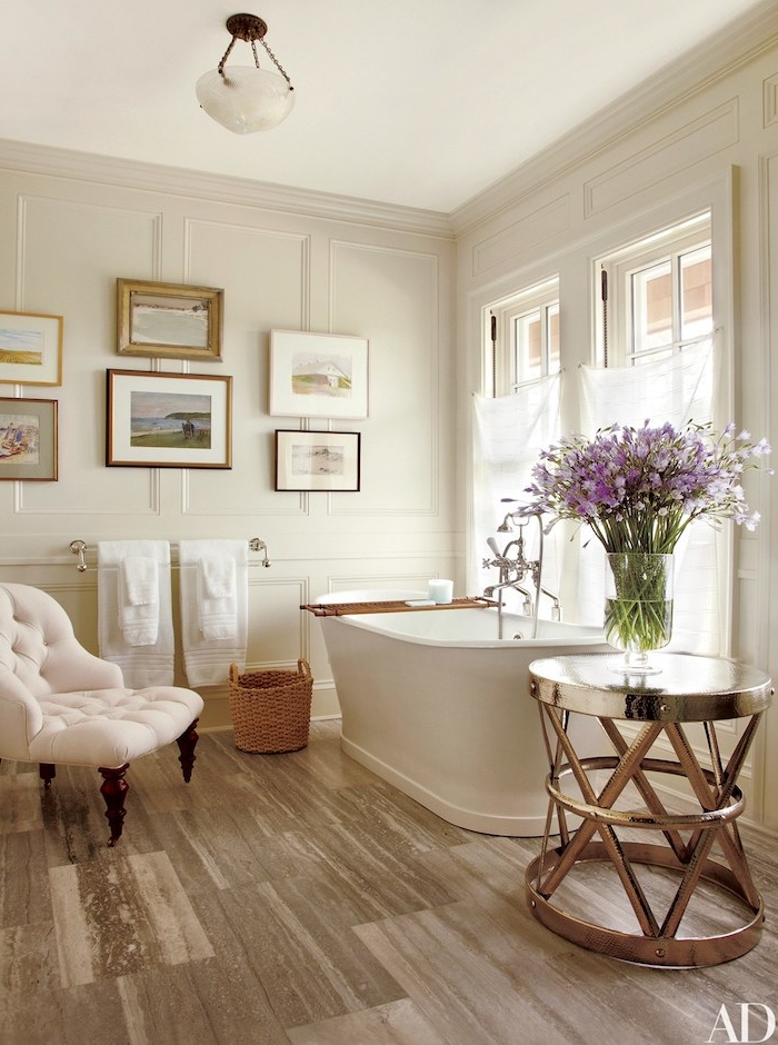 Luxuriöses Badezimmer, weiße Badewanne aus Keramik und metallener Tisch, weißer Ohrensessel und Rattan Korb auf dem Boden, Bilder an der Wand