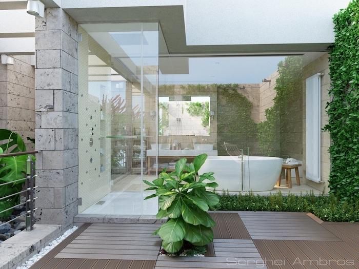 Bad mit großem Fenster, weiße Badewanne, Hocker aus Holz, Steinwand und Grünpflanzen