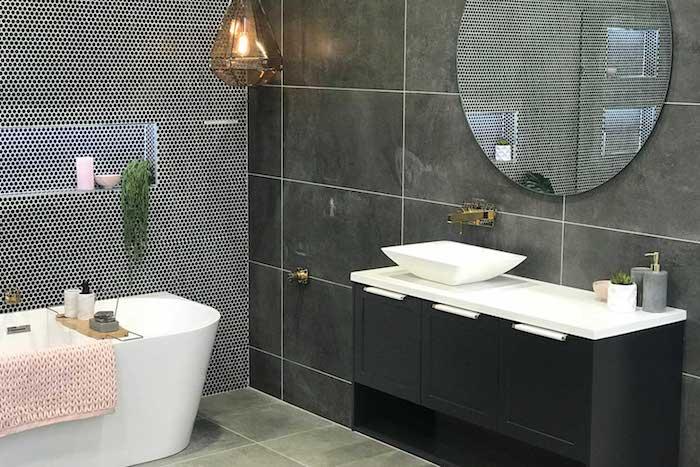 Badeinrichtung Designs, schwarze Fliesen, runder Spiegel, weißer Waschbecken aus Keramik, schwarzer Schrank