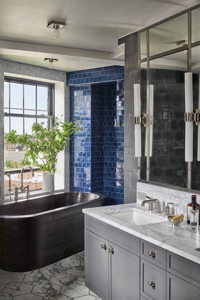 Moderne Bäder, schwarze Badewanne aus Keramik, dunkelblaue Fliesen, Spiegelschrank und Mrmor Waschbecken