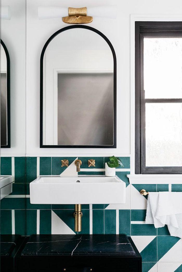 Abgerundeter Spiegel mit schwarzem Rahmen, grünblaue Fliesen und weißer Waschbecken