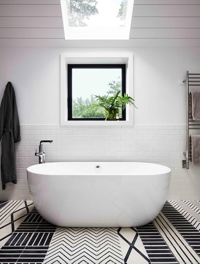 Minimalistische Badeinrichtung, weiße Badewanne aus Keramik, weiße Fliesen
