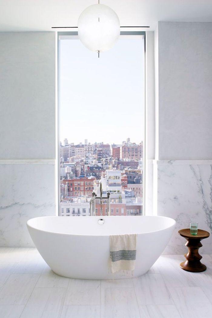 Bad modern gestalten, weiße Badewanne aus Keramik und kleiner Holztisch, großes Fenster und Marmorwand