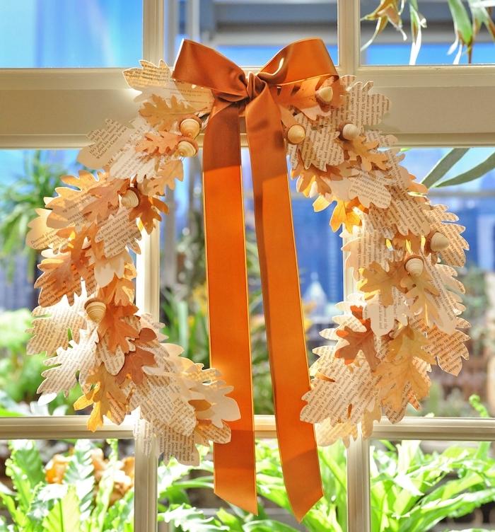 Herbstkranz selber basteln, Herbstblätter aus Zeitungspapier ausschneiden, künstliche Eicheln und orange Schleife