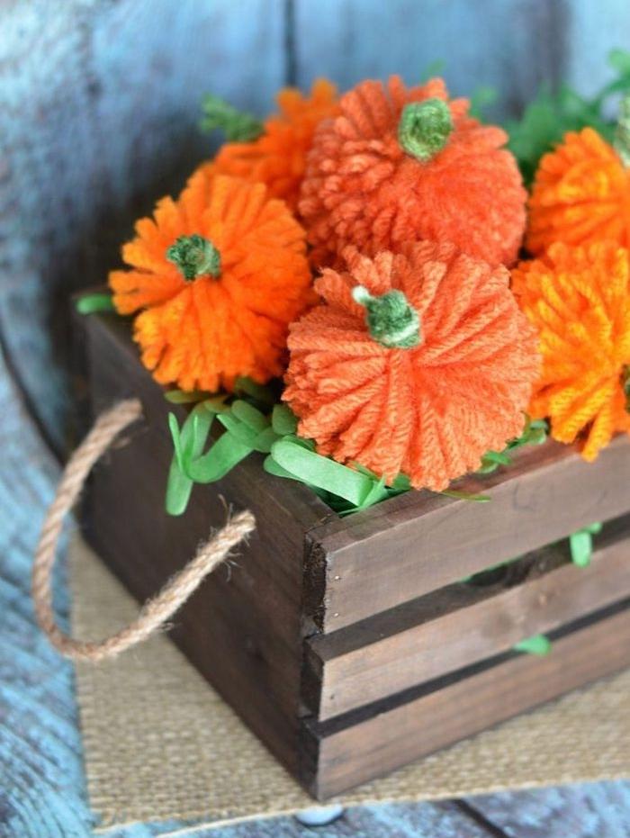Kleine Kürbisse aus Garn selber machen, orange Bommeln, DIY Idee für herbstliche Deko