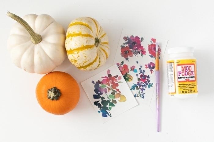 Materialien für herbstliches DIY Projekt, drei Kürbisse, Bastelkleber und Pinsel, Blumen Muster