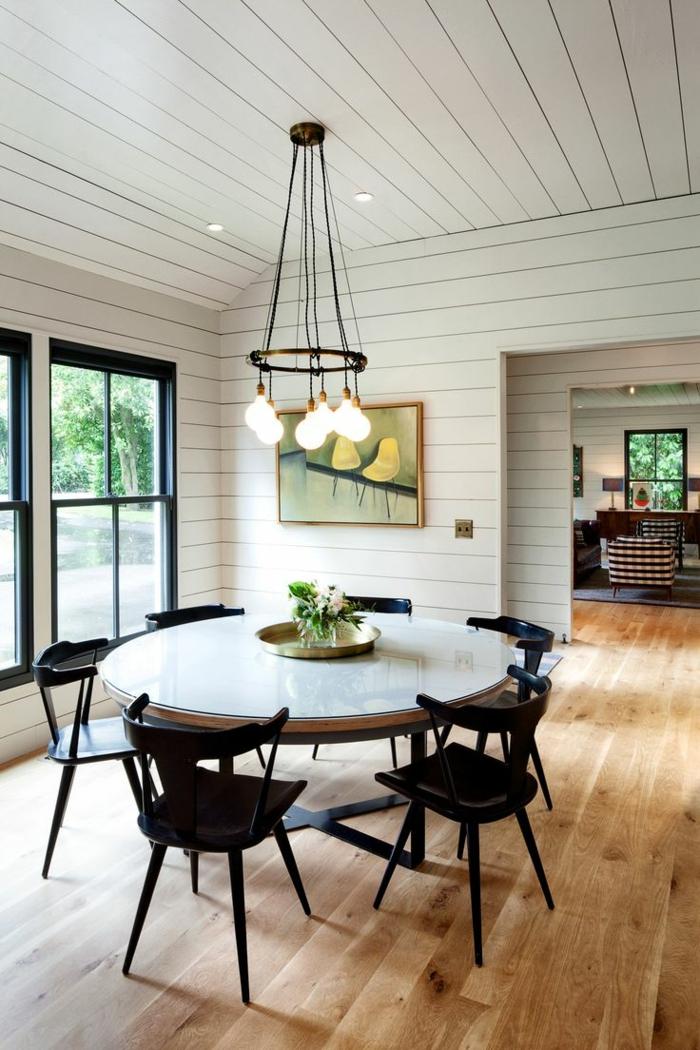 breites-Esszimmer-schwarze-Stühle-hängende-Glühbirnen-Bild-runder-Tisch