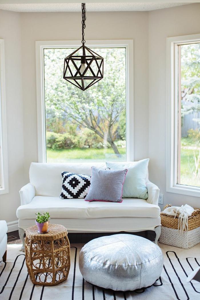 eklektisches-Interieur-Rattanmöbel-weißes-kleines-Sofa-klein-elegant-bunte-Kissen-silberner-Polster-gestreifter-Teppich-Lampe-modernes-Design-Boho-Chic-Elemente