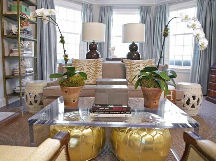 eklektisches-Interieur-gläserner-Kaffeetisch-goldene-Hocker-Orchideen