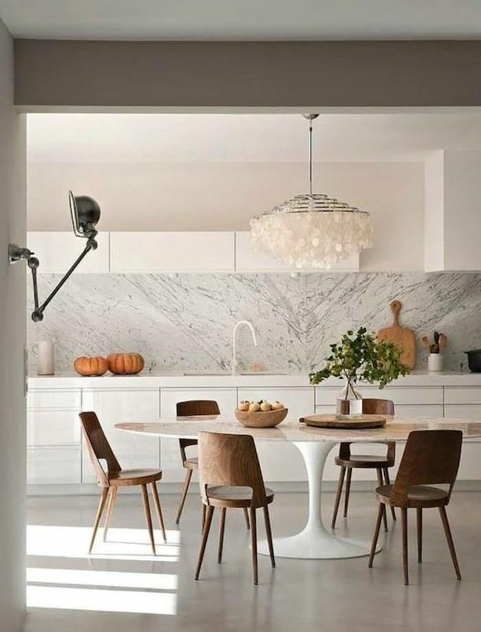 elegantes-Esszimmer-runder-Tisch-effektvoller-Kronleuchter-Designer-Stühle-Kürbisse