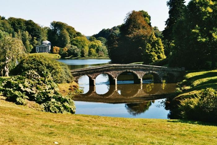 englischer-Garten-Landschaft-Park-Brücke-See-antikes-Gebäude-Bäume-Büsche