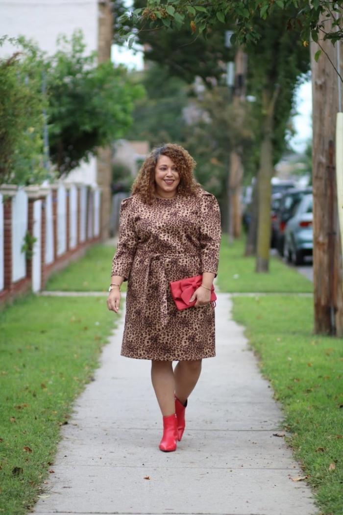festliche mode große damen, knielanges kleid mit tiger muter, rote schuhe und tasche, frisur mit locken
