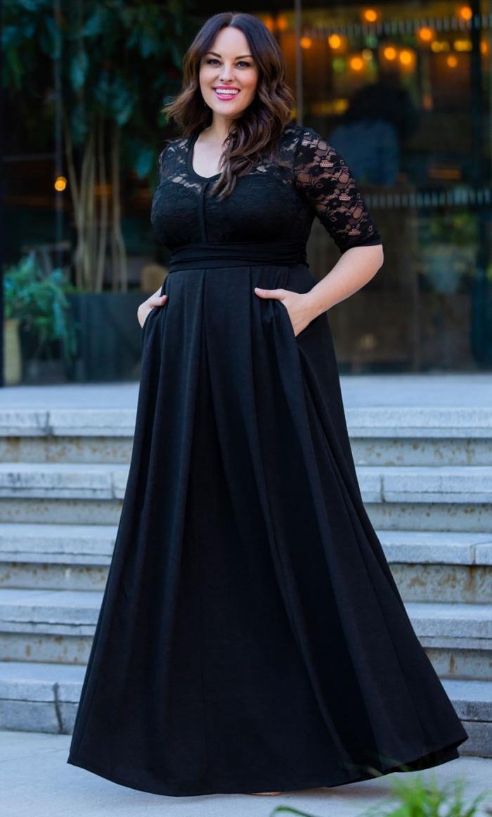 langes schwarzes abendkleid mit hoher teille und ärmeln aus spitze, festliche mode große damen