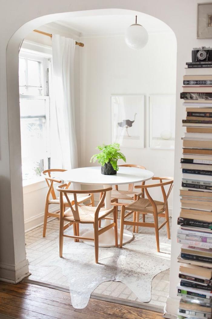 gemütlich-eingerichtetes-Zimmer-weißer-Tisch-hölzerne-Stühle-einfaches-Design-Pflanze-Bücher-Kolonne