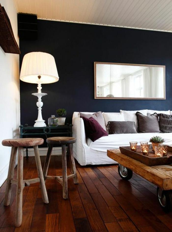 gemütliches-Wohnzimmer-weißes-Sofa-rustikaler-Couchtisch-Holz-Kerzen-Hocker