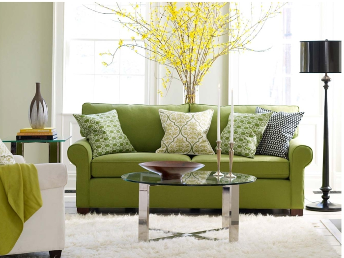grünes-Sofa-passende-Kissen-Couchtisch-gläserne-Tischplatte-hölzerne-Schale-schwarze-Stehlampe-Designer-Vase-flaumiger-Teppich