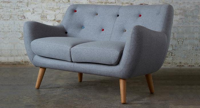 graues-kleines-Sofa-Textil-bunte-Knöpfen-Ziegelwand