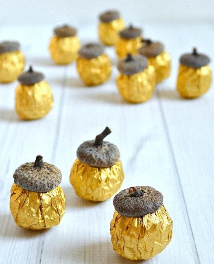 Herbstdeko mit Kindern basteln, Eicheln mit goldener Folie umwickeln, Ideen für Herbstbasteln