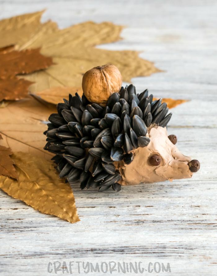 Igel selber machen aus Modelliermasse, Sonnenblumenkerne für Stachel kleben, herbstliche Bastelideen für Kinder