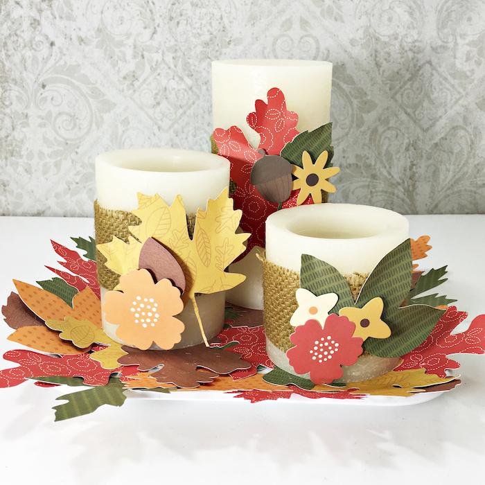 Weiße Kerzen herbstlich dekorieren, mit Herbstblättern, Eicheln und Blumen aus Papier