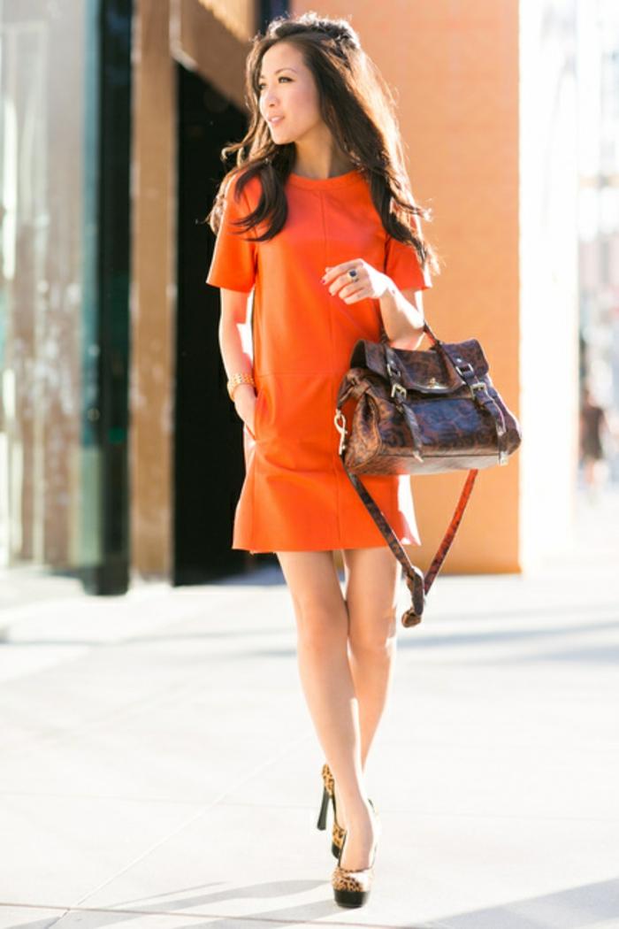 kleid-in-orange-eine-herrliche-frau-mit-einer-tasche