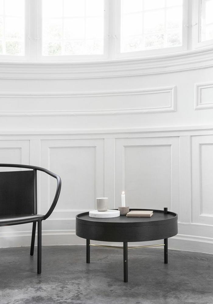minimalistische-Gestaltung-weiße-Wände-runder-Nesttisch-Kerze-schwarze-elegante-Möbel