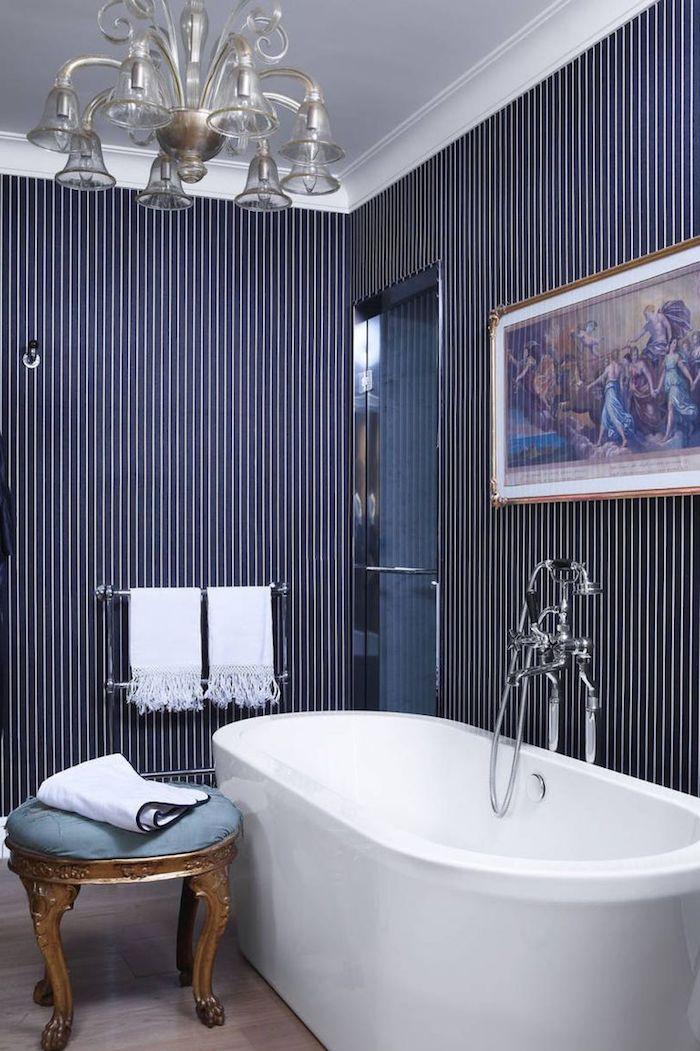Badezimmer modern gestalten, weiße Badewanne aus Keramik, verspielter Kronleuchter, Wandgestaltung weiße und dunkelblaue Streifen