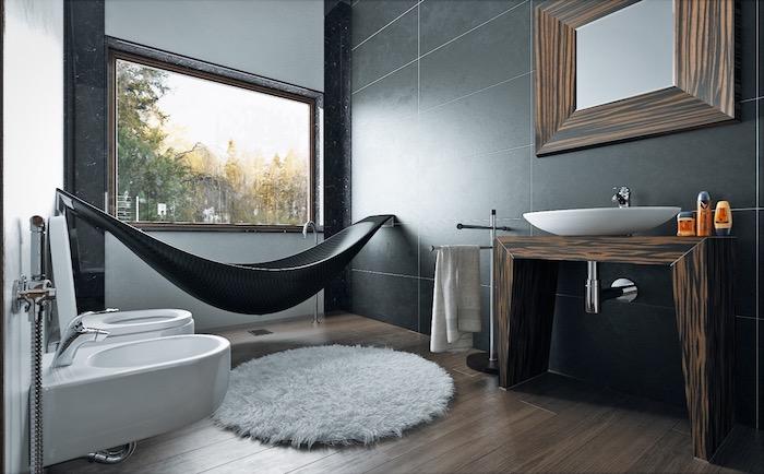 Badewanne in Form von Hängematte, viereckiger Spiegel mit Holzrahmen, Waschbecken aus Keramik, Holzboden und schwarze Fliesen