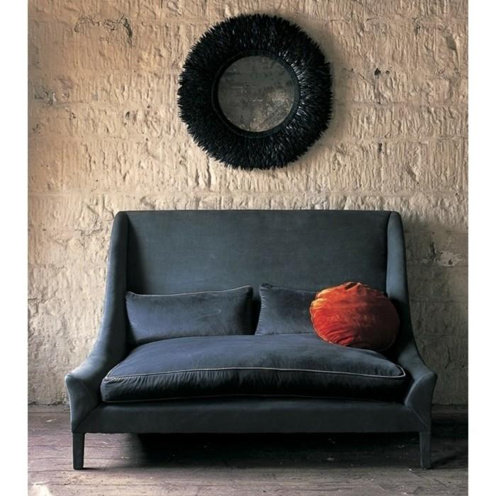 stilvolles-Sofa-dunkelblau-Samt-rundes-orange-Kissen-Wanddekoration-Steinwand