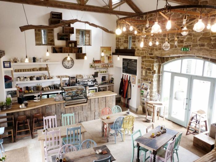 Cafe-modernes-Interieur-landhausstil-möbel-gemütlich-viele-Lichtbirnen-Steinwände