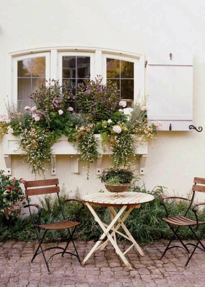 Garten-Tisch-Stühle-Schmiedeeisen-viele-Blumentöpfe-Fensterladen-Holz-weiß