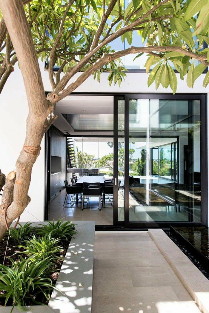 Glastür-moderne-Wohnung-räumlich-sommerliche-Atmosphäre-exquisit-stilvoll-Baum