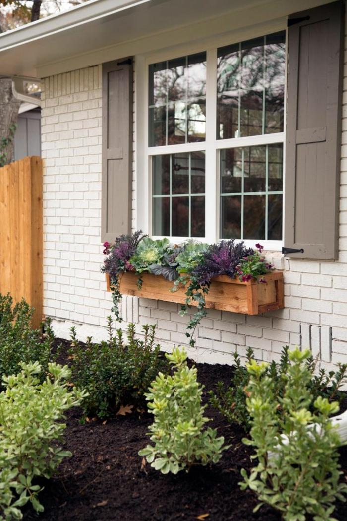 Haus-weiße-Ziegelwände-Topfpflanzen-Garten-braune-Fensterläden