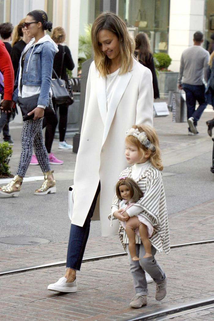 Jessica-Alba-weißer-Mantel-langes-Modell-Jeans-sportlicher-Outfit-kleines-Kind-Puppe