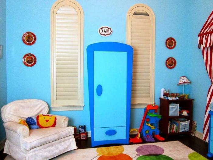 Kinderzimmer-blaue-Wände-Sessel-Spielzeuge-attraktiver-blauer-Kleiderschrank