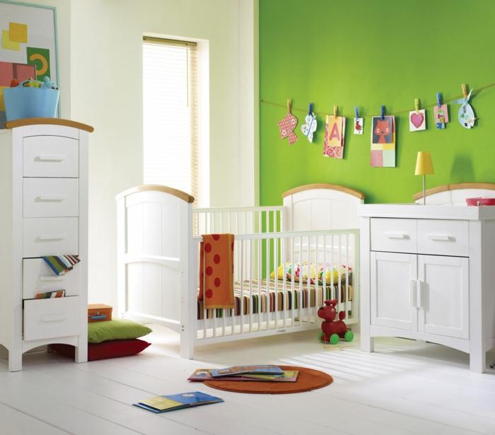 Kinderzimmer-frische-grüne-Wände-lustige-Wanddekoration-Babybett-Schrank-Schubladen-weiße-Möbel-Spielzeuge