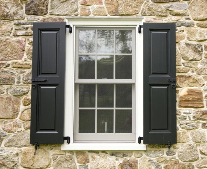 Steinwand-Fenster-schwarze-Fensterläden