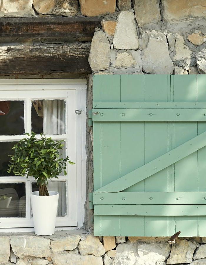 Steinwand-kleines-Fenster-weiße-Fensterrahmen-Topfpflanze-Fensterladen-Holz-frische-grüne-Farbe