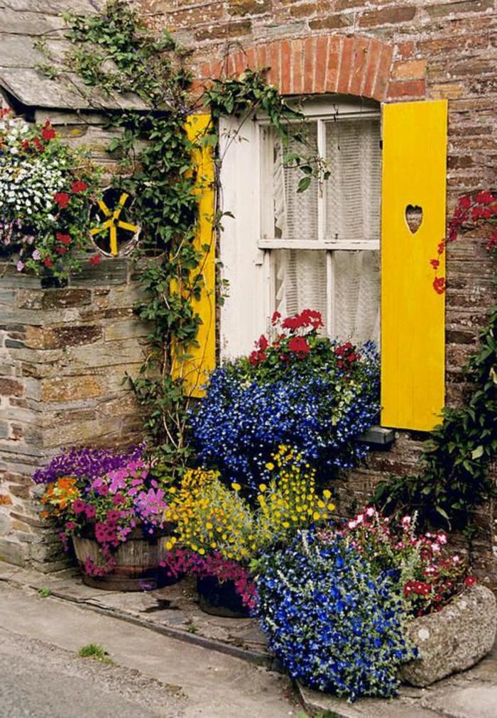 Straße-Italien-romantische-Atmosphäre-Fenster-lustige-gelbe-Läden-Herzen-Dekoration-viele-Blumen