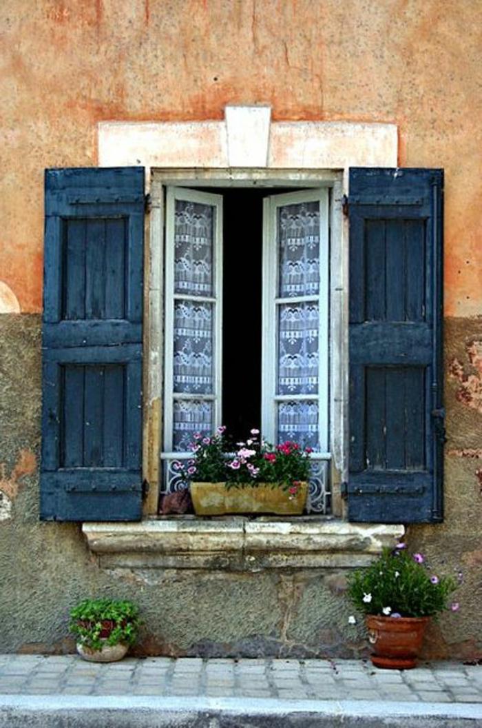 Straße-altes-Gebäude-Fenster-schöne-Gardinen-dunkelblaue-Läden-Blumentöpfe