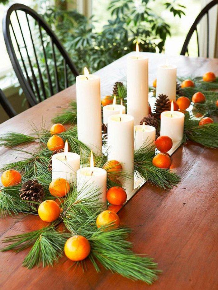 Tischdeko-zu-Weihnachten-Zannenzweige-Orangen-Zapfen-Kerzen