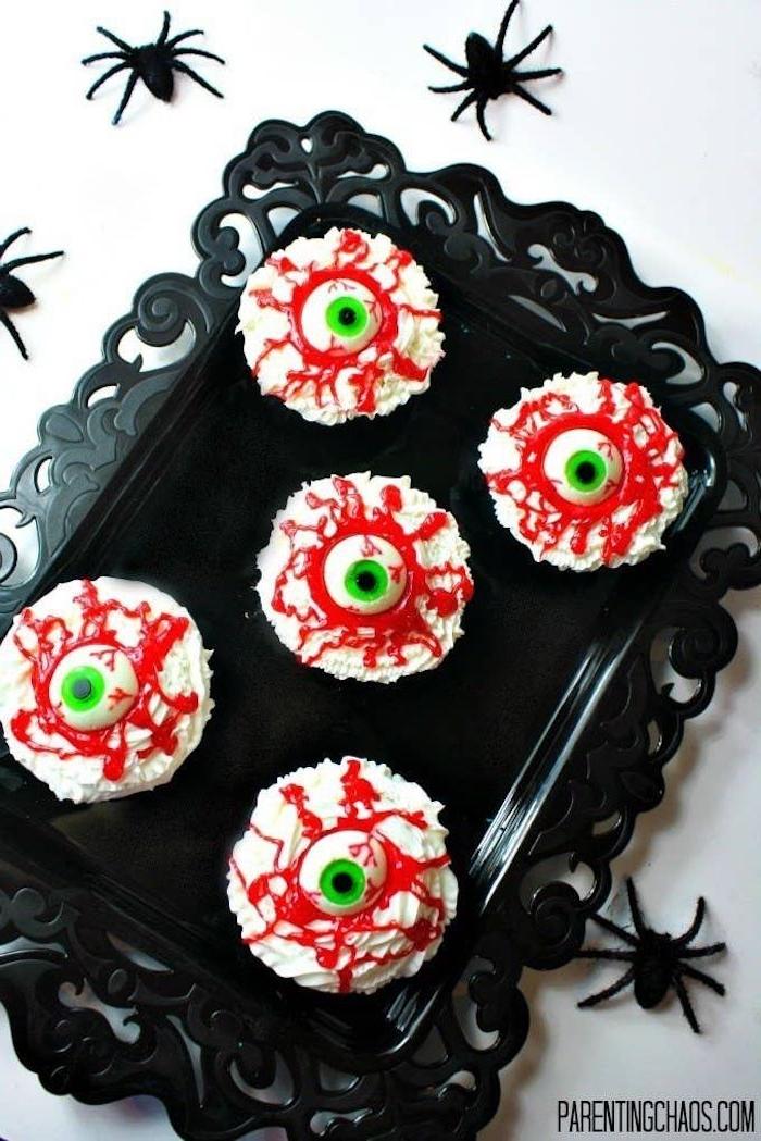 augenapfel cupcakes halloween snack ideen weißer zuckerguss dekoration schwarze spinnen grüne augen ausgefallen backideen lustige muffins