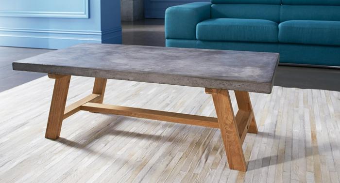 couchtisch-aus-beton-neben-einem-blauen-sofa