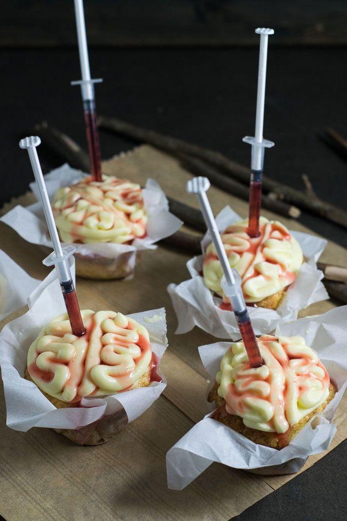 cupcakes weißer zuckerguss gehirn form eingestochene spritzen mit blut halloween backen ausgefallene ideen