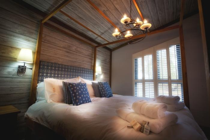 elegantes-Schlafzimmer-stilvoller-Kronleuchter-großes-Bett-blaue-Kissen-Tücher-landhausstil