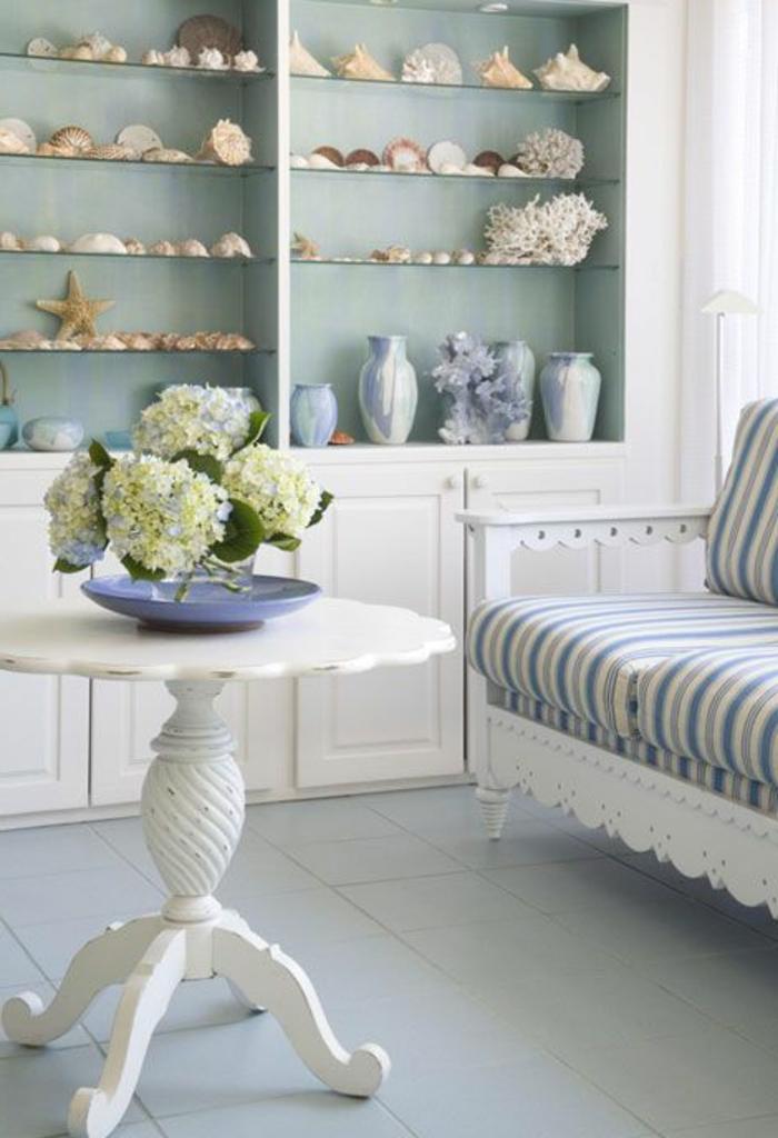 gemütliches-Wohnzimmer-helle-Farbschemen-runder-vintage-Kaffeetisch-Blumen-gestreiftes-Sofa-Regale-Muscheln