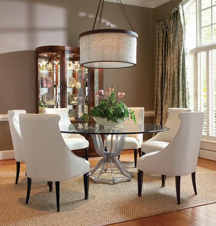 gläserner-Esstisch-rund-Blumen-weiße.Sessel-großartiger-Kronleuchter