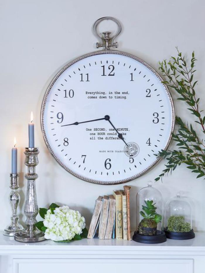 große-Wanduhr-origineller-Spruch-Botschaft-Kerzenhalter-Blumen-Bücher-Pflanzen